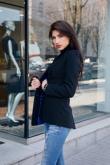Business, people beauty and lifestyle concept - young fashion brunette business woman against business center at sunset. girl in a black jacket and blue jeans. smile, professionalism. sunshine