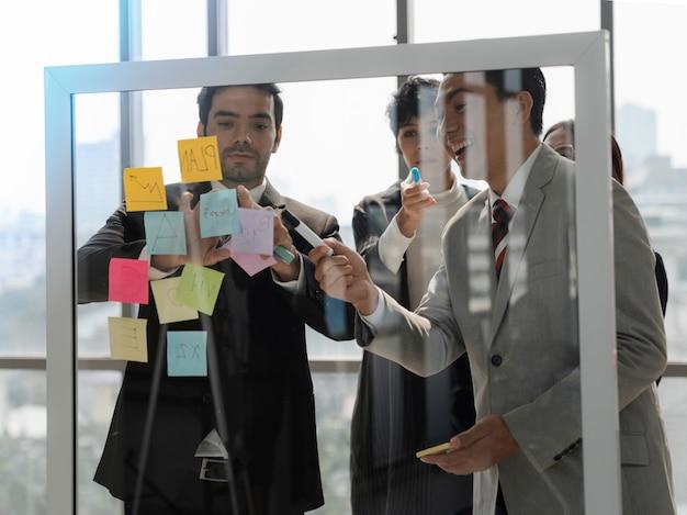투명한 유리벽 뒤에 있는 사업가들은 사무실에서 브레인스토밍과 토론을 하고 아이디어, 팀 계획 또는 새로운 아이디어 사고 개념을 공유하기 위해 스티커 메모를 게시합니다.