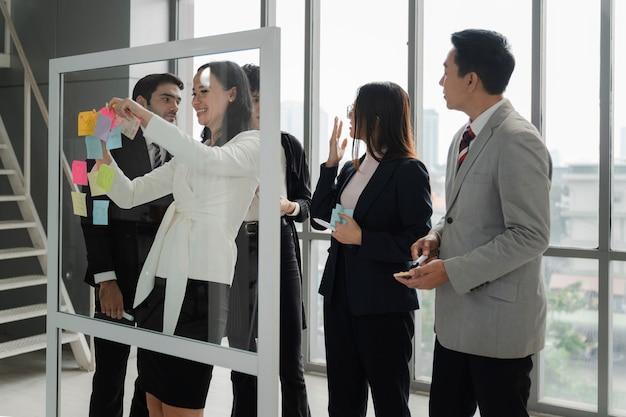 비즈니스 사람들은 사무실에서 브레인스토밍과 토론을 하고 종이 노트를 사용하여 아이디어를 공유하고, 유리 벽에 붙은 메모, 팀 계획 또는 새로운 아이디어 생각 개념을 공유합니다.