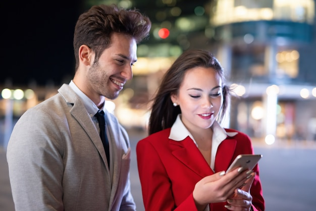 Business people businessman and businesswoman using a smartphone at night in a city