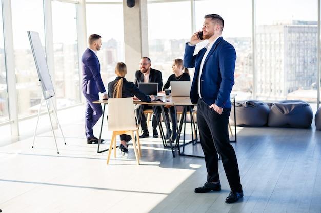 ビジネスマン、ビジネスマンは、高層ビルの近代的なオフィスで一緒に働いています。監督は電話中です。オフィスワークのコンセプト。セレクティブフォーカス