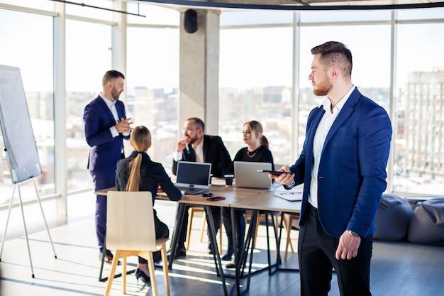 Деловые люди, бизнесмены вместе работают в современном офисе в многоэтажном небоскребе. режиссер разговаривает по телефону. концепция работы офиса. выборочный фокус