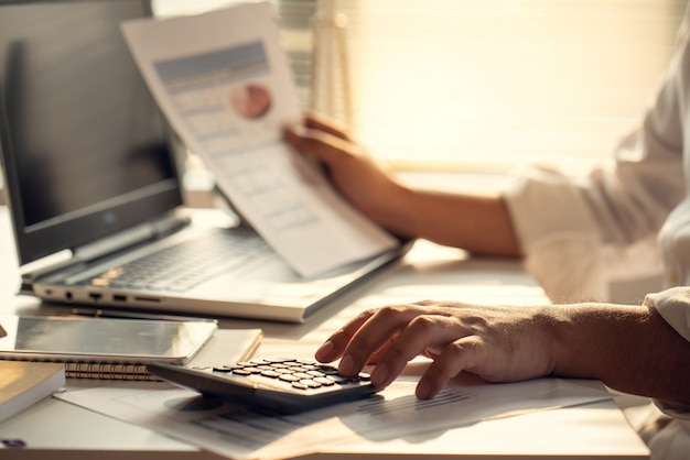 不動産や住宅購入に投資するために利息、税金、利益を計算するビジネスマン