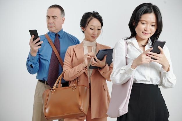 비즈니스 사람들은 소셜 미디어를 확인하거나 스마트폰 및 태블릿 컴퓨터에서 뉴스를 읽고 있습니다.