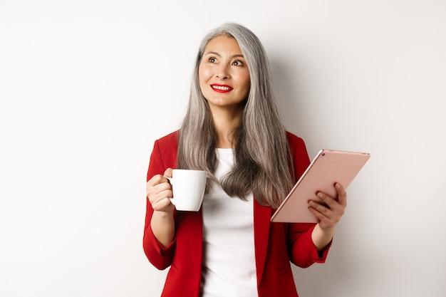 Концепция деловых людей. азиатская коммерсантка пьет кофе и держит цифровую таблетку, задумчиво улыбаясь в верхнем левом углу, на белом фоне.