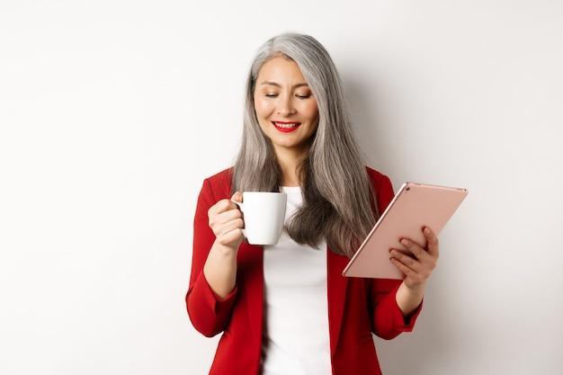 Концепция деловых людей. азиатская зрелая коммерсантка держа цифровую таблетку и смотря кофейную чашку с довольной улыбкой, стоя над белой предпосылкой.
