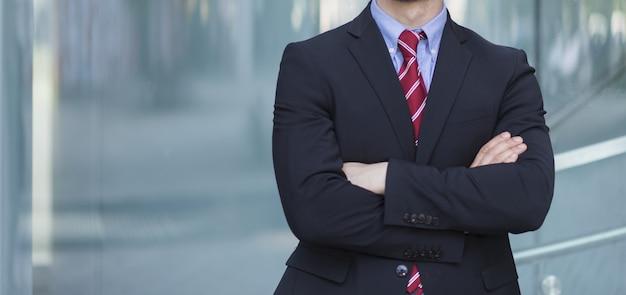 ビジネスパーソンの概念、彼の腕を折り畳む実業家。顔が見えない
