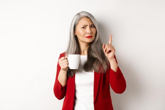 Концепция деловых людей. недовольная азиатская коммерсантка пьет кофе и неодобрительно трясет пальцем, запрещает что-то, стоя на белом фоне.