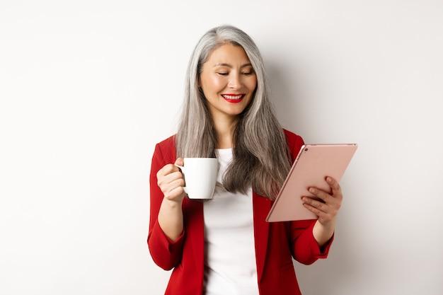 Концепция деловых людей. элегантная азиатская женщина выпивая кофе и чтение на цифровой таблетке, стоя над белой предпосылкой.