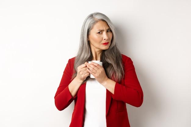 Концепция деловых людей. жадная азиатская коммерсантка защищает ее кофе и хмурится на камеру, стоя на белом фоне.