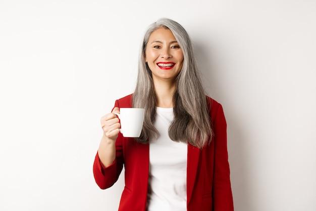 Концепция деловых людей. счастливый азиатский бизнесмен в красном пиджаке улыбается, пить кофе из кружки, стоя на белом фоне.