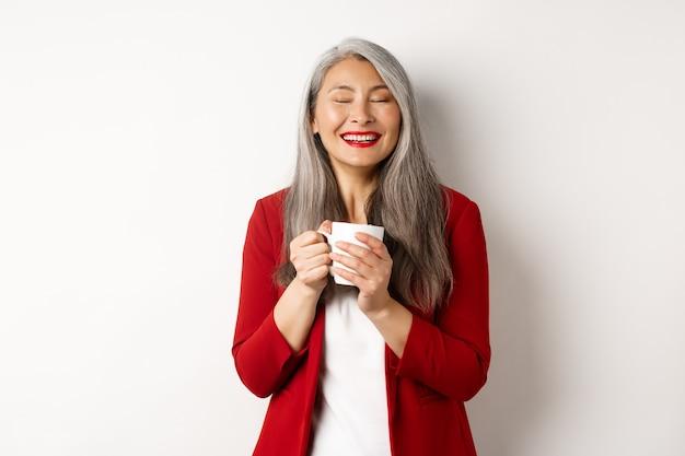 Концепция деловых людей. счастливая офисная дама в красном пиджаке, наслаждаясь пить кофе, держа кружку и улыбаясь в восторге, стоя над белой стеной.