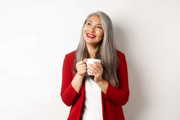 Концепция деловых людей. улыбаясь азиатской бизнес-леди перерыв на кофе, держа теплую кружку и глядя в верхнем левом углу мечтательный, белый фон.