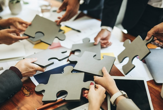 Business people connecting puzzle pieces together