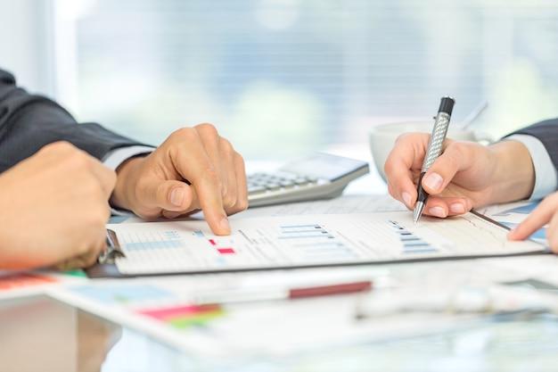 비즈니스 사람들이 테이블에 앉아 계산기를 세고 있습니다.