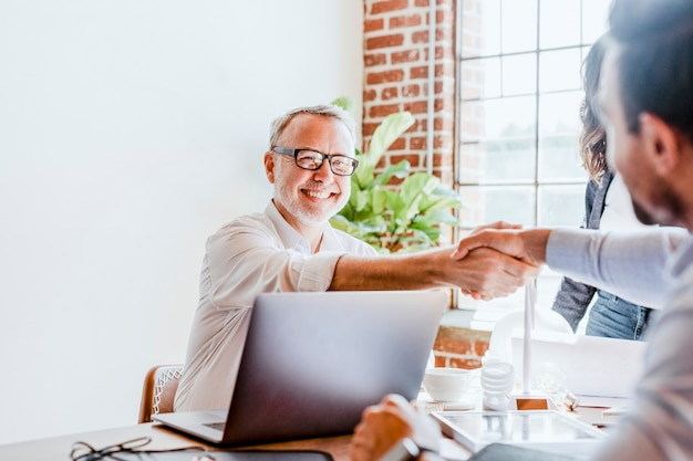 Business people cut the deal by shake hands