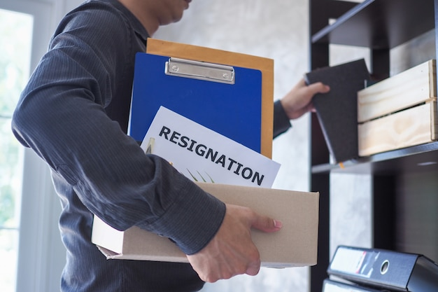 Business people decide to quit. collecting personal items and resignation letters in boxes
