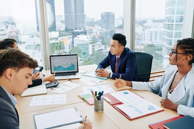 会議でグラフを議論するビジネス人々