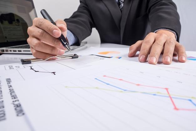 Деловые люди обсуждают финансовые графики - крупным планом выстрел из рук за стол