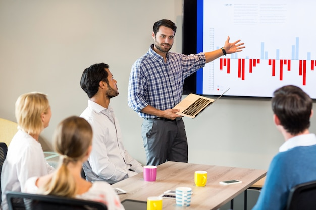 Business people discussing over graph during a meeting