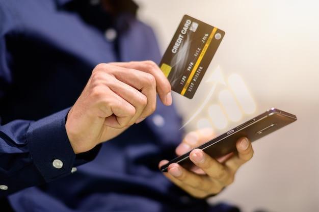 ビジネスマンはスマートフォンにグラフの表を表示し、クレジットカードを使用します