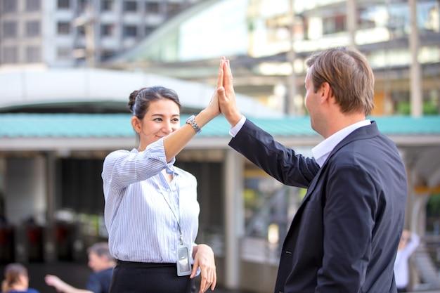 Business people doing hi-five on achievement against building.