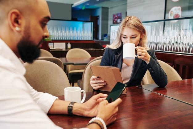 コーヒーを飲み、オフィスカフェでタブレットコンピューターやスマートフォンでニュースや記事を読んでいるビジネスマン