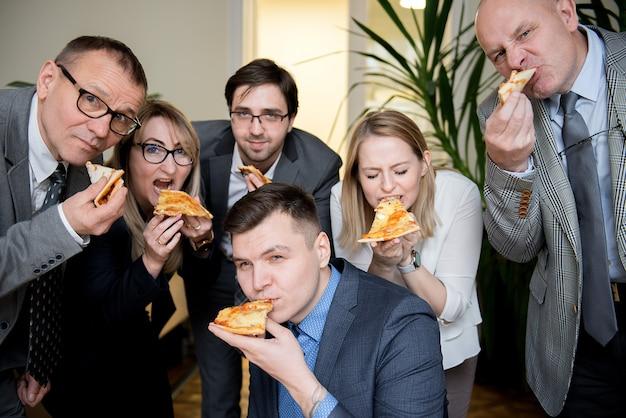 Деловые люди едят пиццу в офисе
