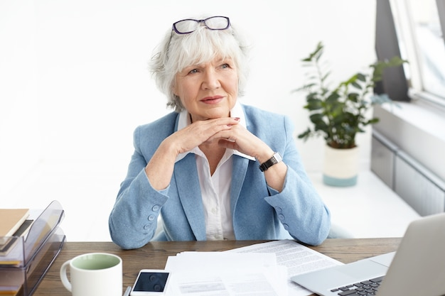 ビジネス、人、電子ガジェット、最新テクノロジーのコンセプト。ノートパソコンでデスクで作業しながら物思いにふける表情を持っているフォーマルな服装で経験豊富なシニア白人女性ceoの屋内ショット