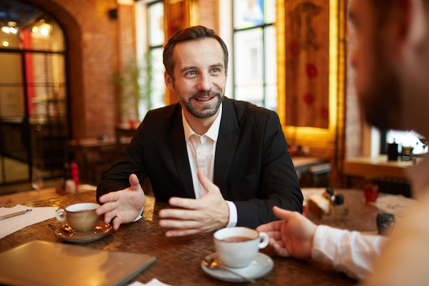Деловые люди наслаждаются перерывом на кофе в ресторане