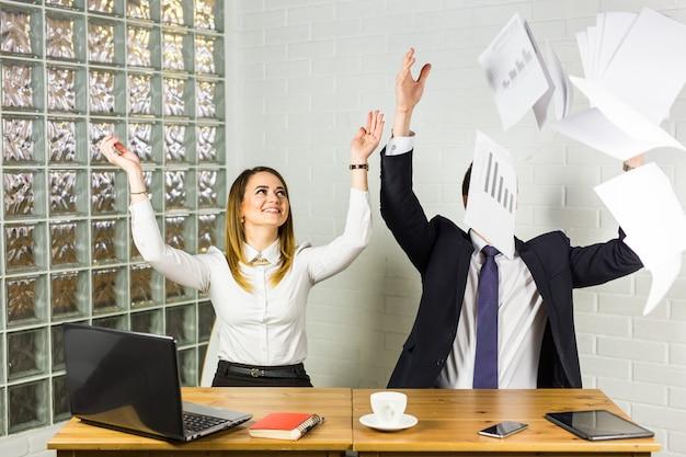 ビジネス人々は幸せな笑顔を興奮させて、紙を投げ、ドキュメントは空中を飛ぶ、成功チームのコンセプト