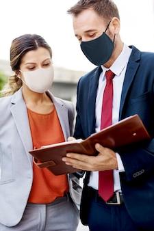 Uomini d'affari in maschera facciale che lavorano nella nuova normalità