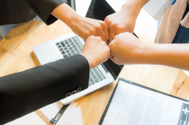 Business people fist bump to synergy and teamwork concept