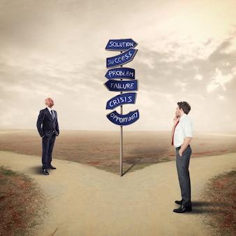ビジネスマンは方向矢印に従います。ビジネスの成功への道を見つける