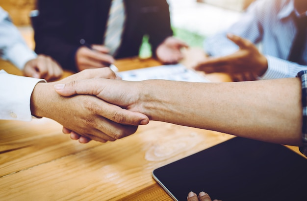 Business people friendly handshake at group meeting in the room.