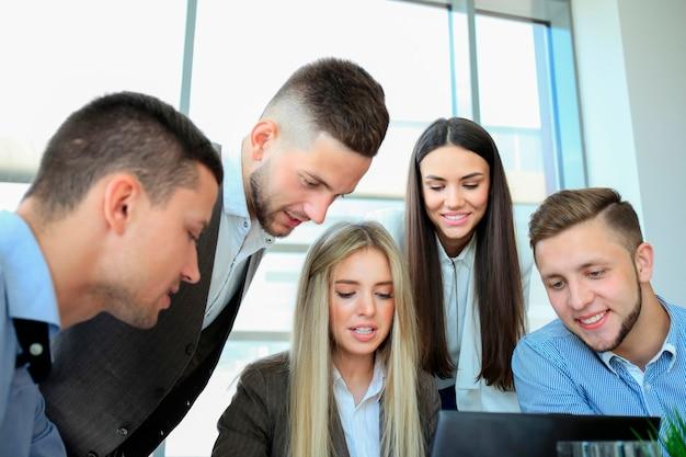 Деловые люди собрались вокруг ноутбука, обсуждая в офисе