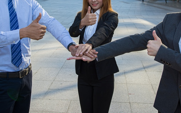 Business people giving thumb up and stack hands together in teamwork.