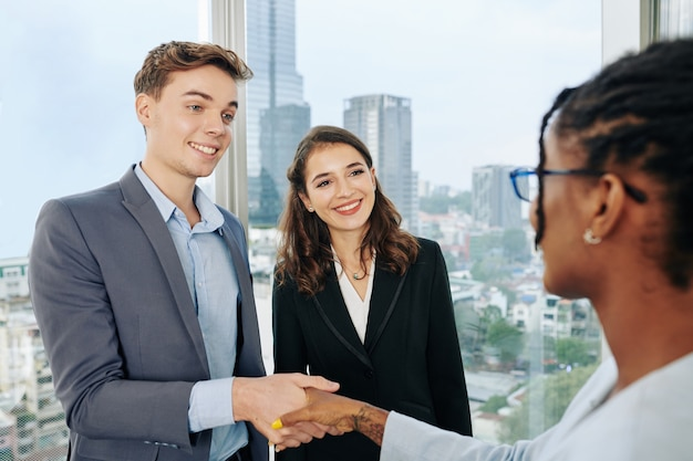 Business people greeting new coworker