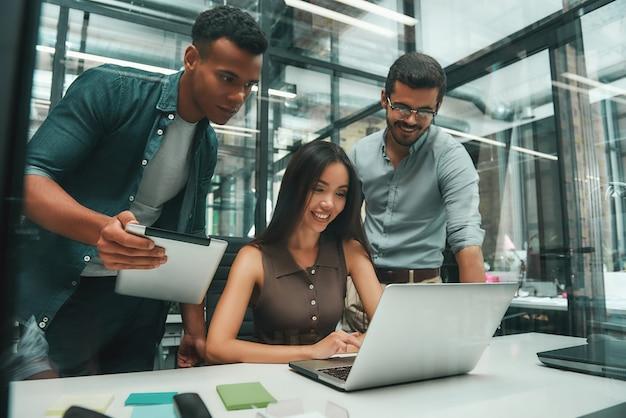 일하는 동안 현대 기술을 사용하는 3명의 젊고 쾌활한 직원으로 구성된 비즈니스 사람들 그룹