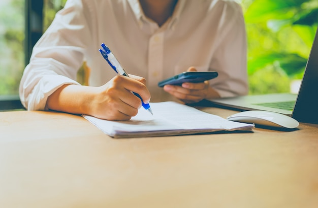 ビジネス人々の手持ち株携帯電話とテーブルの上のラップトップコンピューターで書類を埋める。