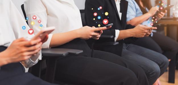 ビジネスの人々は、スマートフォンを使用して手し、アイコンソーシャルメディアを表示します。ネットワーク技術の概念。