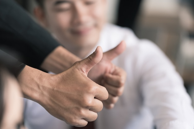 Business people hands giving thumb up in the meeting.