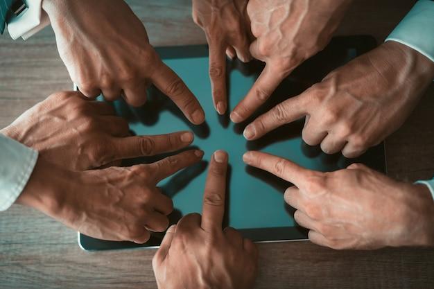 Руки деловых людей касаясь экрана цифрового планшета на деревянном столе