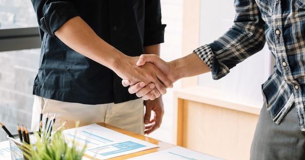 ビジネスの合併と買収のチームワークのためのビジネス人々ハンドシェイク