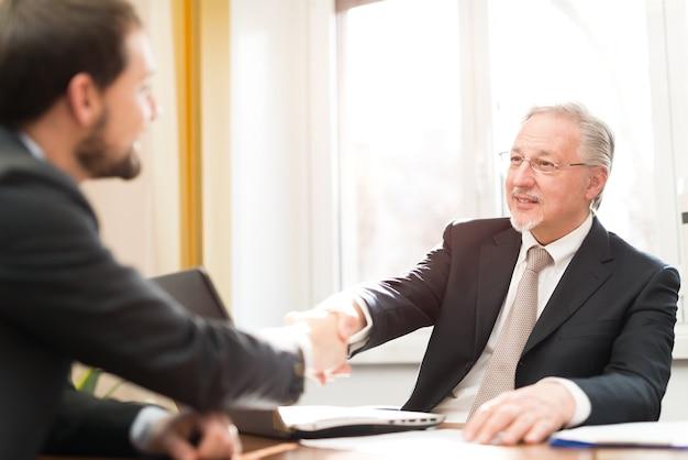 Рукопожатие деловых людей в их офисе