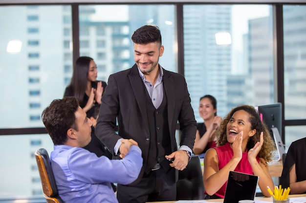 Business people handshaking in office against colleague