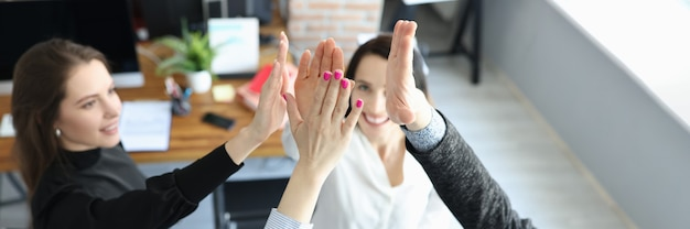 Business people happily give each other five in office