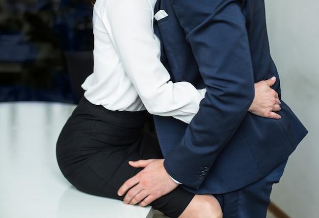 ビジネスの人々はオフィスのテーブルで性的活動をしています