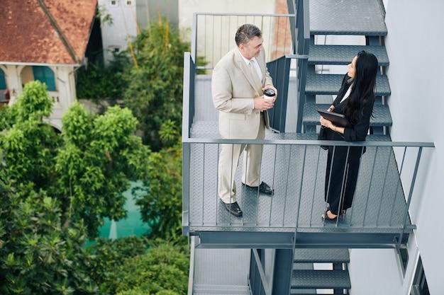Деловые люди во время перерыва на кофе на лестнице пожарной лестницы и обсуждают последние новости