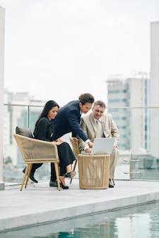 スイミングプールで会議を持ち、ノートパソコンの画面でプロジェクトの概要について話し合うビジネスマン